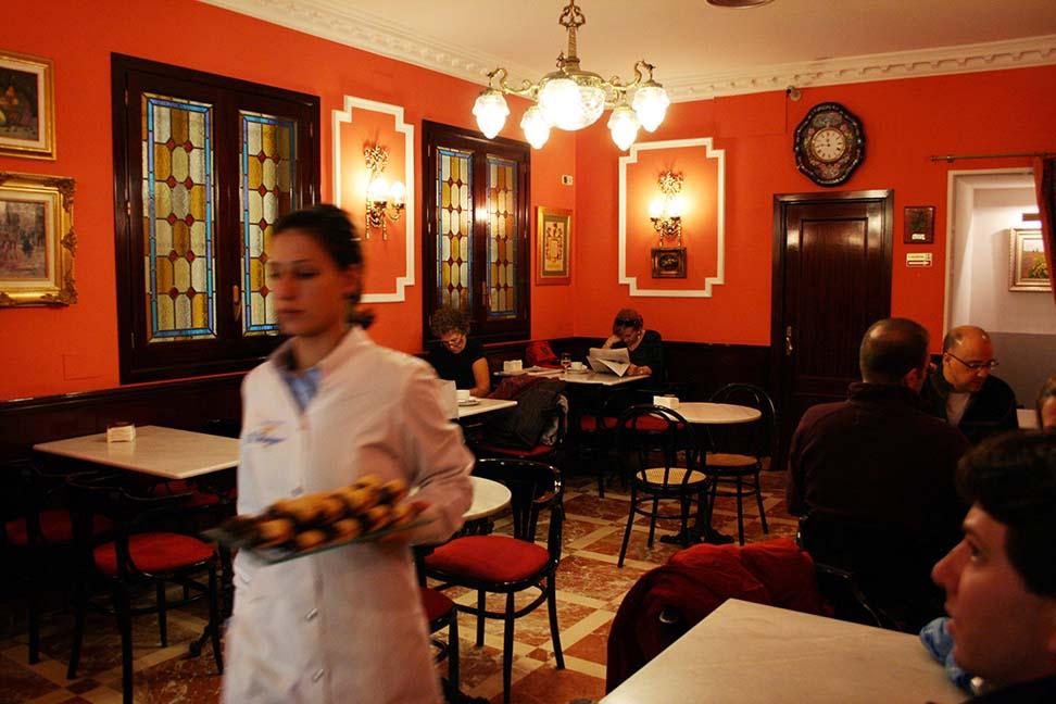 En el Salón de Té de El Riojano una camarera lleva una bandeja de pasteles.