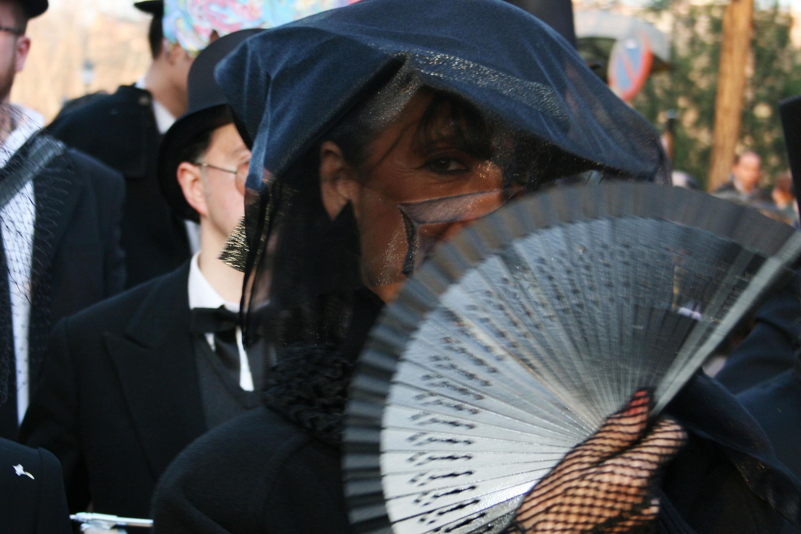 Señora del cortejo fúnebre del entierro de la sardina se oculta tras un abanico