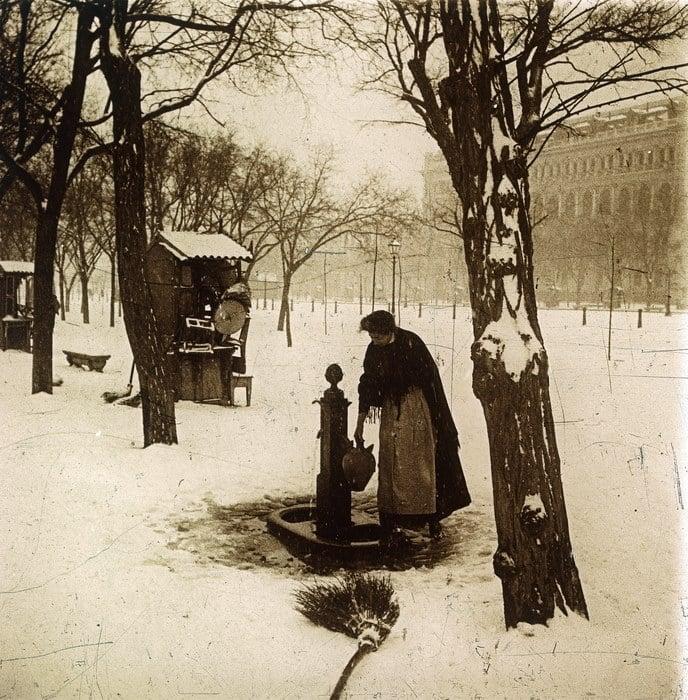 Imagen de una señora recogiendo agua en una fuente del Paseo del Prado en un día de nieve